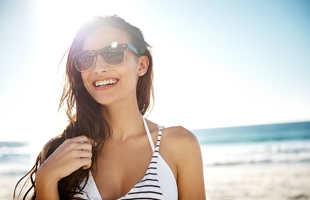 20 something fit, confident looking woman smiling at beach