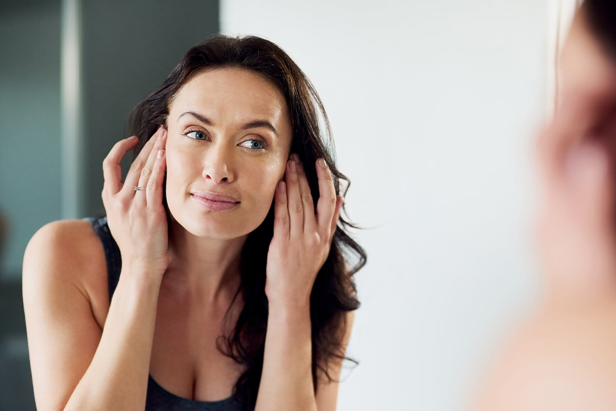 woman gazes at her naturally healthy skin in mirror