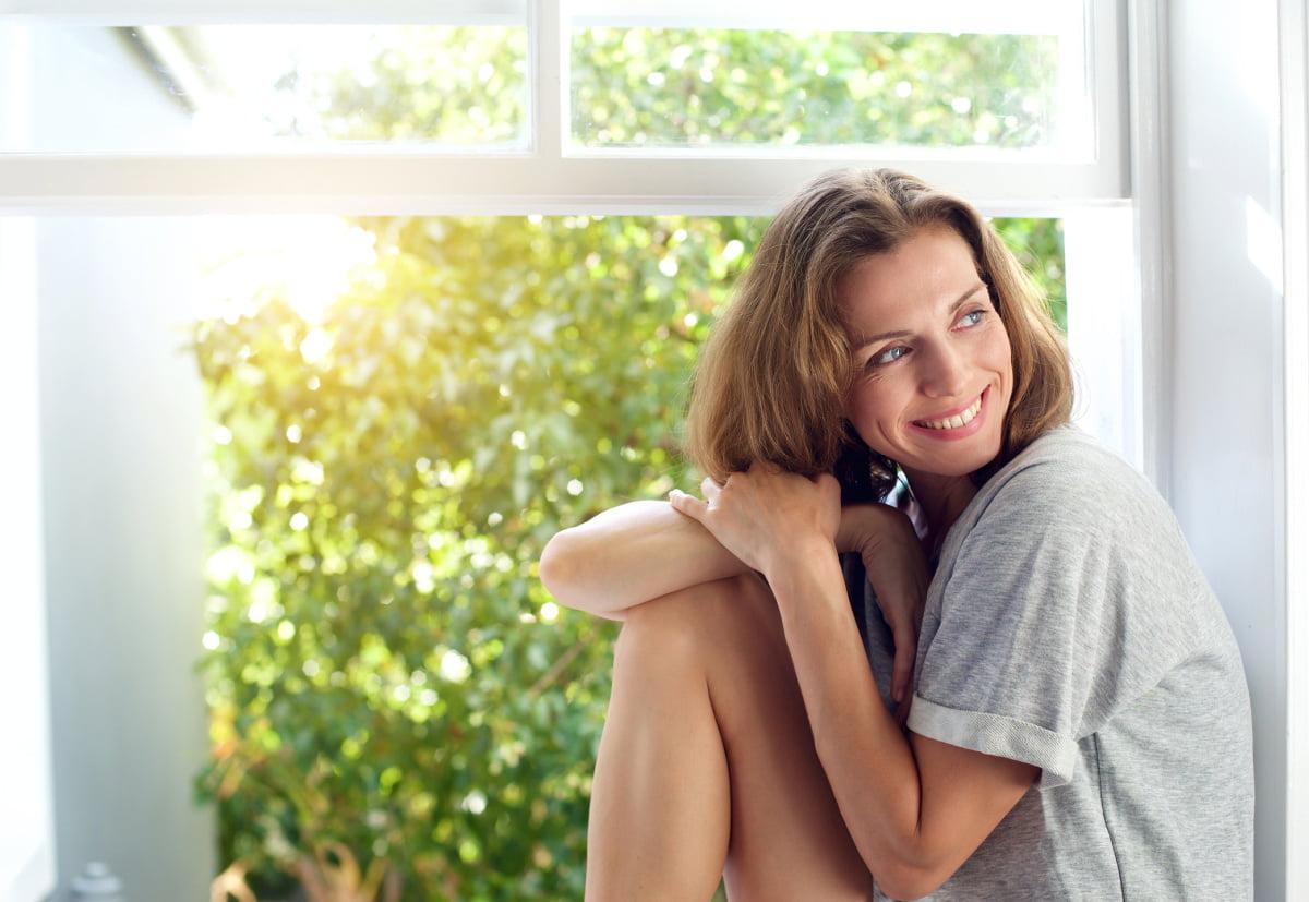 Happy Woman Smiles Next to Sunlit Window