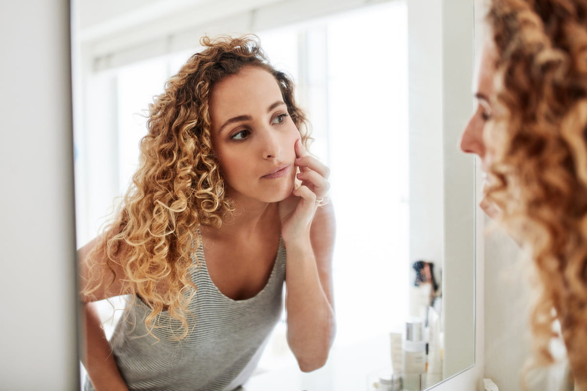 Woman Checks Dermal Fillers in Mirror for Sign of Movement and Migration