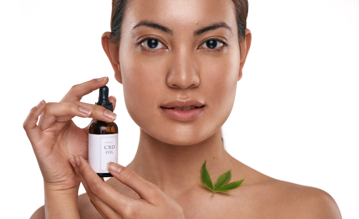 Beautiful Woman with Glowing Skin Holds bottle of CBD Oil for Skincare and Acne